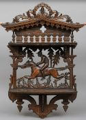 A carved Black Forest wall shelf The scroll carved crest above two hinged shelves, the back worked