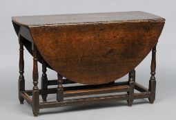A late 18th/early 19th century oak gate-leg table The oval twin flap top supported on block and