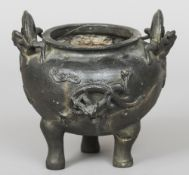 A Ming Dynasty Chinese bronze censor Robustly cast with applied dragons, standing on tripod feet,