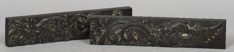 A pair of Chinese carved hardwood scroll weights One worked with a phoenix, the other with a dragon.
