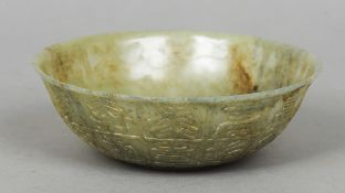 A Chinese carved green and russet jade bowl The exterior worked with archaic script.  15 cm