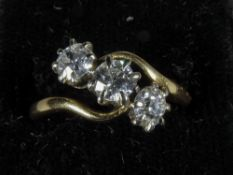 A diamond set 18 ct gold three stone crossover ring The central stone approximately 0.25 carat;