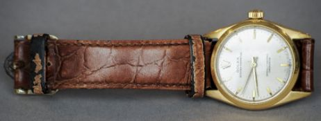 An 18 ct gold Rolex Oyster Perpetual mid-size wristwatch The signed silvered dial with baton