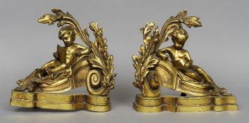A pair of gilt bronze chenets Modelled as reclining putti reading.  30 cm wide.  (2) CONDITION