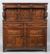 An 18th century oak court cupboard The moulded rectangular top above a carved frieze and twin