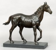 A bronze model of a horse Naturalistically modelled, standing on a black marble plinth base.  44