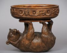 A carved Black Forest bear centre bowl The reclining beast supporting a flowerhead carved bowl.
