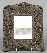A Victorian bronze mirror frame Decorated with cherubs and putti.  29 cm high. CONDITION REPORTS: