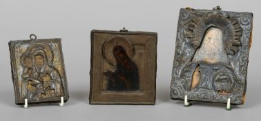 Three Russian metal mounted and painted icons Two depicting Jesus, the other the Madonna and Child.