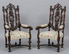 A pair of Jacobean style carved open armchairs The ornately pierced and carved backs issuing twin