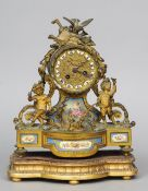 A 19th century gilt metal and Sevres type porcelain inset mantel clock The repousse dial headed with