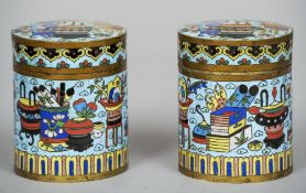 A pair of Chinese cloisonne caddies and covers Of circular section decorated with precious objects.