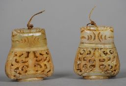 A pair of Chinese carved jade pomanders Each with pierced baluster body and cover.  5.5 cms