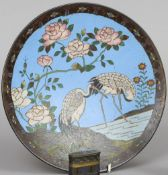 A Chinese cloisonne plate Typically decorated with cranes in a river landscape with floral