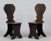 A pair of George III oak hall chairs, in the Italian Renaissance style With solid shaped back and
