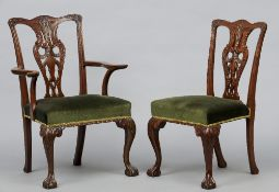 A set of ten mahogany dining chairs Each with curved top rail and shield back above the over-stuffed