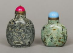 Two Chinese carved hardstone snuff bottles  Both with coloured hardstone stoppers.  8 cm and 6.5