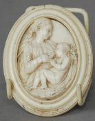 A 19th century Dieppe carved ivory plaque Formed as a mother breast feeding her child.  8 cm high.