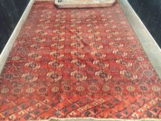 A late 19th century Teke wool rug With five rows of guls on a terracotta pink ground within