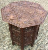 An Eastern carved hardwood folding table The top and sectional base pierced and carved with fruiting