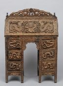 A 19th century Chinese carved hardwood bureau Profusely carved with dragons and mythical beasts.  78