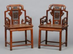 A pair of late 19th century Chinese carved hardwood open armchairs Each pierced  back centred with a