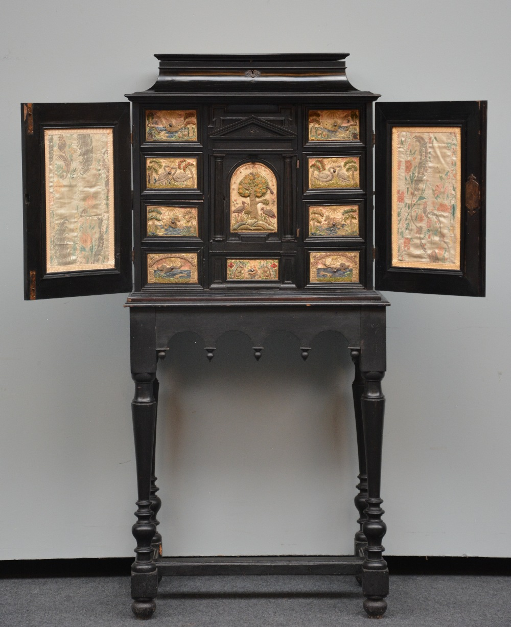 An exceptional 17thC Flemish ebony and rosewood cabinet-on-stand, silk embroidered inside, the