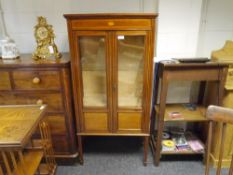 An Edwardian string inlaid mahogany vitrine cabinet, the frieze centred by an oval patera, over a