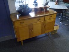 An Ercol light elm small sideboard, with one long and one short drawer above a pair of cupboard