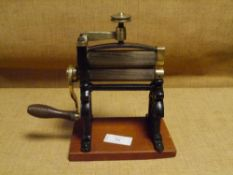 A miniature cast iron and brass model of a mangle, with turned wooden handle and mounted on a wooden