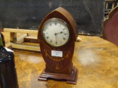 An early 20th century inlaid mahogany mantle clock, the shaped lancet case with stylised foliate and