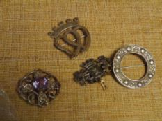 A group of silver brooches comprising: a luckenbooth brooch; a Celtic brooch of kilt pin type; a