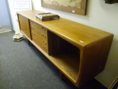 A 1960's teak sideboard, with a bank of four central drawers flanked by sliding doors. 0.80m by 2.