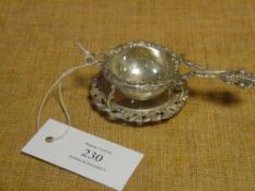 A late 19th century Continental silver tea strainer on stand, the strainer with fleur de lys