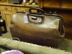 An early 20th century leather Gladstone bag, with brass fittings, reinforced corners and brass