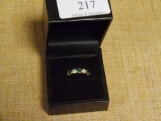 An emerald and diamond five stone ring, set with three collet-set round cut emeralds spaced by a