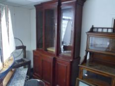 A 19th century mahogany breakfront bookcase, the moulded cornice above three glazed doors, the