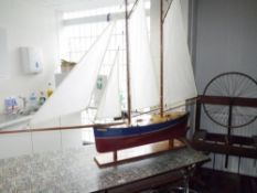 A painted wooden pond yacht, twin masted, with brass fittings, on an oak stand. Height 1.13m, length