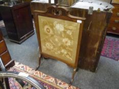 An Edwardian mahogany framed firescreen, with scroll and fret carved crest, raised on hipped