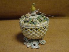 An 18th century porcelain pot pourri, possibly Derby, of oval form, the floral-encrusted cover
