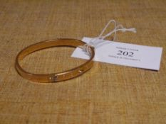 "A 15ct gold ""buckle"" bangle. 9.9 grams"