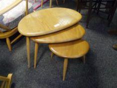 "A set of three Ercol light elm ""Pebble"" nesting tables."