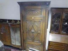 A late 19th century carved oak hall wardrobe, with gadroon and lion mask carved cornice above a