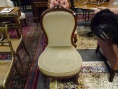 A mid-Victorian walnut-framed nursing chair, the oval back with leaf and scroll carved crest, raised