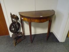 A George III mahogany demilune foldover tea table, with serpentine frieze and raised on stop-
