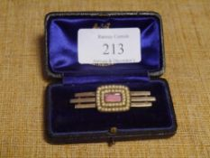 An Edwardian pink engine-turned enamel and seed pearl brooch, the oval enamel panel within twin