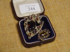 """A late Victorian Scottish shield brooch/pendant set to the centre with a """"Cairngorm"""" within collet"""