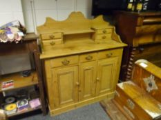 A stripped pine dresser in 19th century style, the superstructure fitted with drawers, the base with