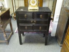 A Chinese black lacquered small chest, fitted with two short over three long drawers, raised on