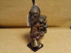 An African carved wooden tribal figure, possibly Congo, the head with horn surmount, bearing pods